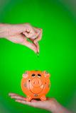 Holding coin over piggy bank Stock Image