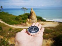 Holding on a compass showing your direction and your navigation by facing to the ocean. A compass is an instrument used for navigation and orientation that shows royalty free stock images