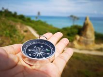Holding on a compass showing your direction and your navigation by facing to the ocean. A compass is an instrument used for navigation and orientation that shows royalty free stock photography