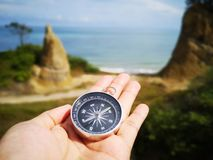 Holding on a compass showing your direction and your navigation by facing to the ocean. A compass is an instrument used for navigation and orientation that shows stock photos