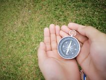 Holding on a compass showing your direction and navigation . A compass is an instrument used for navigation and orientation that shows direction relative to the stock photo