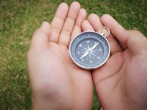 Holding on a compass showing your direction and navigation . A compass is an instrument used for navigation and orientation that shows direction relative to the stock images