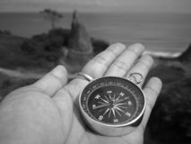 Holding on a compass showing your direction and your navigation by facing to the ocean. A compass is an instrument used for navigation and orientation that shows stock images
