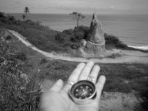 Holding on a compass showing your direction and your navigation by facing to the ocean. A compass is an instrument used for navigation and orientation that shows royalty free stock image