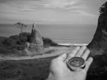 Holding on a compass showing your direction and your navigation by facing to the ocean. A compass is an instrument used for navigation and orientation that shows stock image