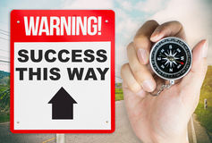 Holding compass for the way to success warning Stock Images