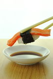 Holding crab stick sushi roll with chopsticks and shoyu sauce Royalty Free Stock Images