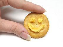 Holding a cracker with a smile Royalty Free Stock Images