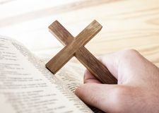 Holding the cross. Man holding the cross with bible royalty free stock photo