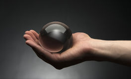Holding a Crystal Ball. Hand holding a clear transparent crystal glass ball in their palm Stock Photos