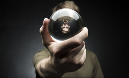 Holding a Crystal Ball. Young man holding a clear transparent crystal glass ball in their hand Stock Photo