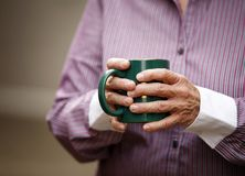Holding a cup. Hands of elderly woman with arthritis holding cup Royalty Free Stock Photos