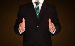 Holding dell'uomo d'affari qualcosa Fotografia Stock