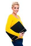 Holding della giovane donna il suo computer portatile chiuso Fotografia Stock