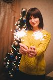 Holding der jungen Frau funkelt in ihren Händen nahe Weihnachtsbaum Stockbilder