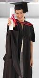 Holding di laurea della giovane donna il suo diploma Fotografie Stock Libere da Diritti