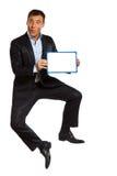 Holding di salto dell'uomo di affari che mostra whiteboard Fotografia Stock