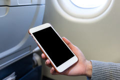 Holding digital mobile phone at airplane. Holding digital mobile phone at the airplane Stock Images