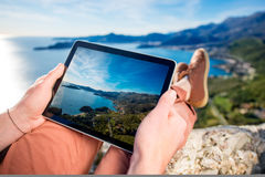 Holding digital tablet on the mountain Royalty Free Stock Photos