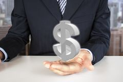 Holding dollar sign. Businessman holding 3d dollar sign in the hand Stock Images