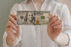 Holding 100 dollars. Woman holds 100 dollars in front of her, official look, money in her hands, bill in the foreground, blurred girl, manicure royalty free stock photo
