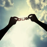 Holding a dream in sky. The word dream is holding by hand in the sky Royalty Free Stock Image