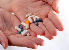 Holding Drugs!. Hands holding a lot of pills over a white background Stock Images