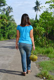 Holding Durian Fruit. Lady's back walking in countryside with Durian fruit hanged in a rope stock photo
