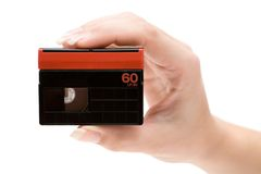 Holding a DV Cassette. Woman holding a mini dv cassette. Isolated on a white background Royalty Free Stock Image
