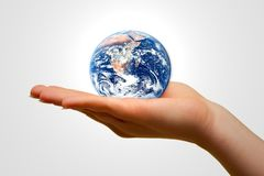 Holding the Earth. Concept of hands holding the Earth. Isolated hands and Earth on gray-white background Royalty Free Stock Photography