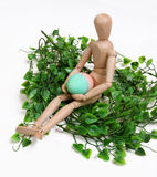 Holding the Egg. Mannequin holding an easter egg in a nest Stock Photo