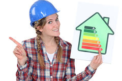 Holding an energy consumption label. Craftswoman holding an energy consumption label royalty free stock photo