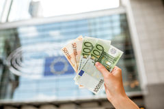Holding euro banknotes. On the european union flag background on the parliament building in Brussel Stock Images