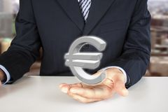 Holding euro sign. Businessman holding 3d euro sign in the hand Royalty Free Stock Image