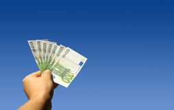 Holding Euros. Hand holding seven 100 Euro notes.  Blue sky background Stock Images