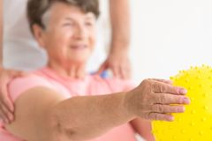 Holding exercise ball in physiotherapy. Blurry portrait of an elderly women in physiotherapy with focus on her hand holding a silicone exercise ball Stock Photo