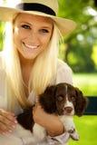 Holding femminile sorridente il suo cucciolo. Fotografia Stock