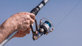 Holding a fishing pole. Hands rewinding a fishing pole reel stock images