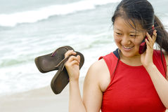 Holding flip flops, chatting on cell phone Stock Photo