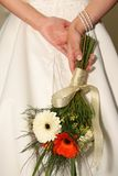 Holding Flowers. Bride holding bouquet behind here back royalty free stock images