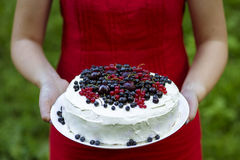 Holding a fresh berry cake. Women holding a fresh berry cake royalty free stock image