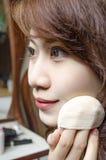 Holding-Gesichtspuderbilden der jungen Frau Lizenzfreies Stockbild