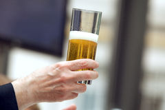 Holding a glass of beer Stock Photos