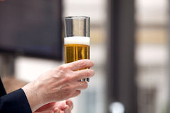 Holding a glass of beer stock photo