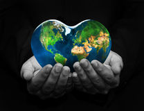 Holding the globe. In a shape of a heart Stock Photo