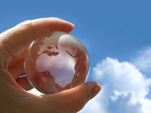 Holding globe. Hand holding a transparent little globe on sunny day stock images
