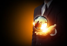 Holding a glowing earth globe Stock Photography