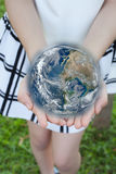 Holding a glowing earth globe in hand Stock Photo