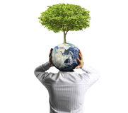 Holding a glowing earth (NASA) globe and tree in his hand Stock Photos