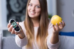 Holding glucometer and apple Royalty Free Stock Photo
